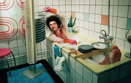 man in tub washing dishes