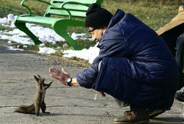 man plays with squirrel